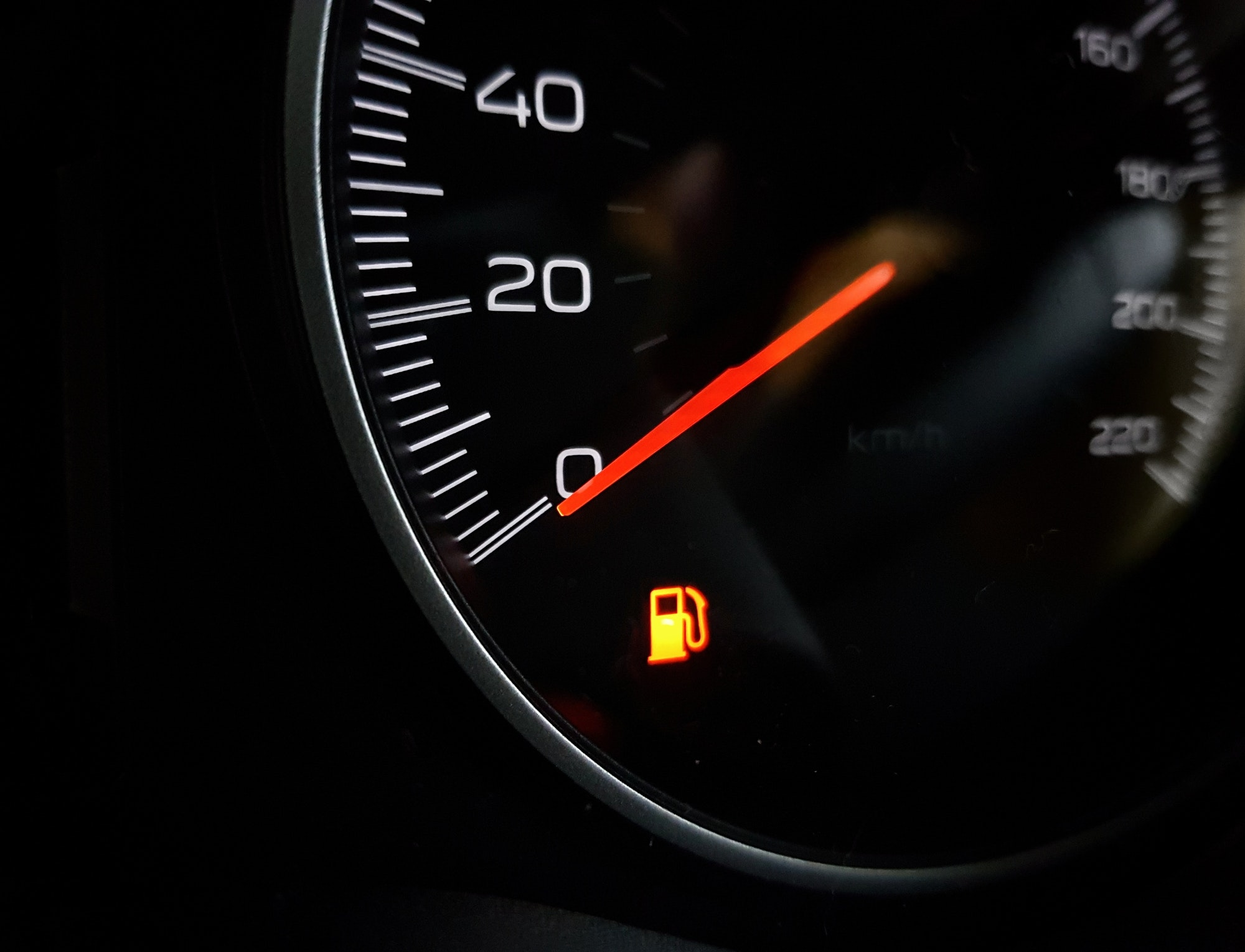 Orange low fuel indicator on a car dash