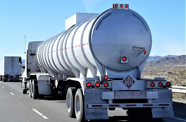 Transportation and Logistics! A big rig truck hauling a silver tanker trailer with a HAZMAT placard